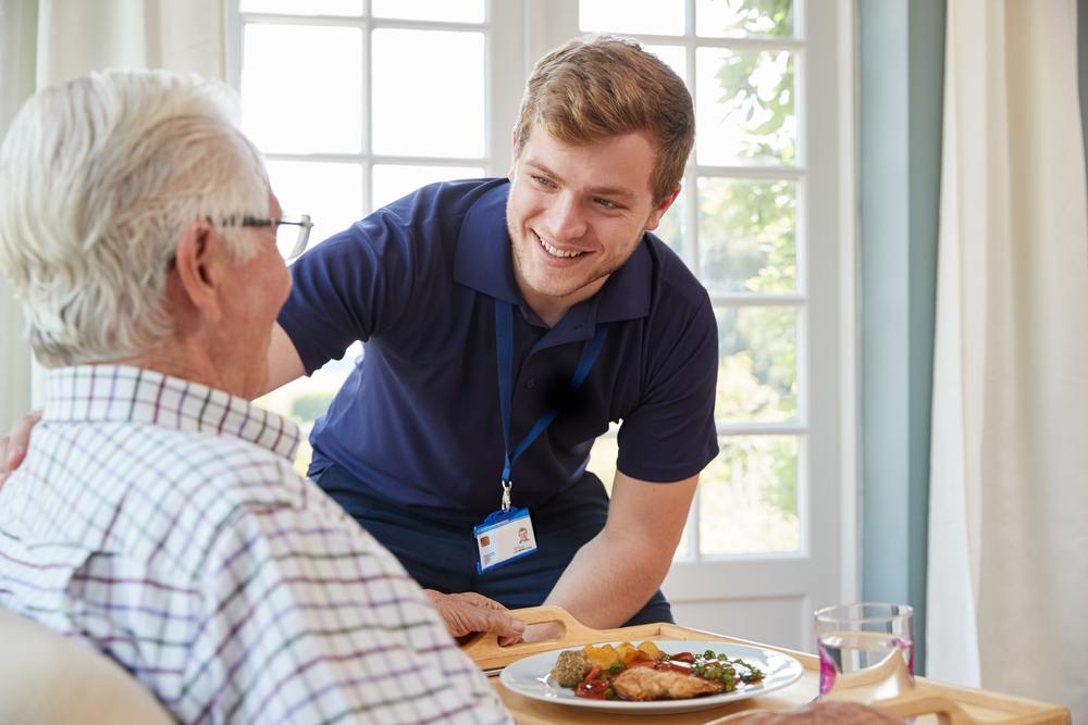 A carer chats to an elderly man as he serves him a meal